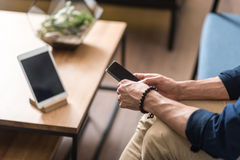Youthful guy using mobile phone inside sitting room. Close up of hands of young man holding smartphone. He is sitting on sofa near table with tablet lying on it Royalty Free Stock Photo