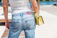 Youthful lady in casual style standing near swimming pool. Close up of back of woman wearing jeans with usa flag. Little yellow handbag hanging on long chain Stock Images