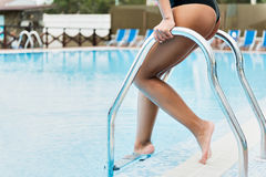 Youthful lady relaxing on summer resort. Close up of legs of young woman going down stairs into swimming pool. She is holding metal hand-rail while dipping into Royalty Free Stock Images