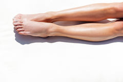 Youthful lady taking tan outdoor. Close up of barefoot legs of young woman lying straight on beach sand. She is sunbathing on resort Stock Image