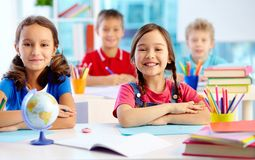 Youthful learners. Portrait of two diligent girls looking at camera at workplace with schoolboys on background stock photos