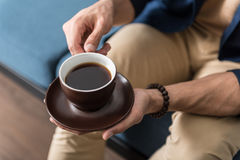 Youthful man spending time with favourite beverage at home. Close up of hands of young guy sitting on cozy couch and drinking coffee. He is holding saucer with Stock Photos