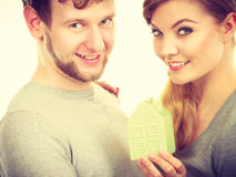 Youthful pair with house model. Property ownership family future finances mortgage bank concept. Youthful pair with house model. Young lady with men posing Stock Photography