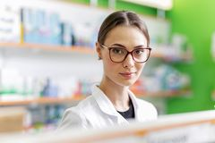 A youthful pleasant dark-haired girl with glasses, wearing a medical overall,stands next to the shelf in a modern stock photo