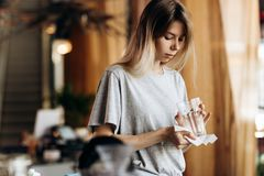 A youthful pretty blonde girl,dressed in casual style, holds a clean glass and looks at it in a modern coffee shop. stock image