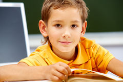 Youthful reader. Portrait of smart lad looking at camera during reading lesson Royalty Free Stock Photography