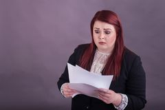 Youthful business woman looking down at stack of papers worried expression. Youthful red haired business woman wearing black suit looking down at stack of paper royalty free stock photo