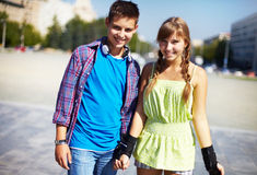 Youthful roller skaters. Couple of two happy roller skaters looking at camera outside Royalty Free Stock Photos