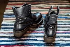Back view of two robust, black ankle leather boots on a colorful rug as a concept of blisters royalty free stock photos