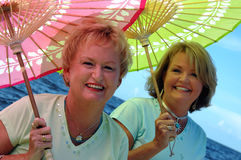 Youthful senior sisters. Two mature women with colorful parasols by the ocean royalty free stock photography