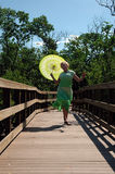 Youthful senior woman. A mature woman skipping on a boardwalk with a parasol royalty free stock photos