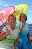 Youthful senior women. Two mature women with colorful parasols by the ocean royalty free stock photo
