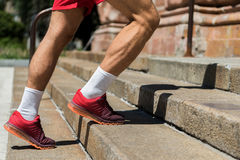 Youthful sporty guy jogging upstairs outdoor. Close up of muscular legs of young athlete going up stone ladder with handrail. He is wearing training shoes and Stock Photo