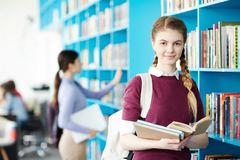 Literature lover. Youthful student with open book looking at camera while choosing literature for lesson Stock Photos