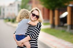 Youthful tender mom with her cute toddler girl. Young mother holding her little daughter standing in front of their house. Happy family together. Youthful tender royalty free stock photos