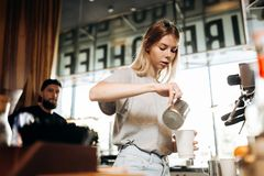 A youthful thin blonde girl,wearing casual cothes,is shown adding milk to the coffee in a cozy coffee shop. royalty free stock images