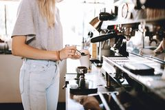 A youthful thin blonde lady,wearing casual clothes,stands nexrt to the coffee machine in a cozy coffee shop. stock photography