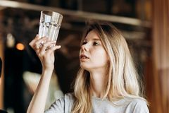 A youthful thin blonde,wearing casual outfit,is looking attentively at the clean glass in a cozy coffee shop. stock photo