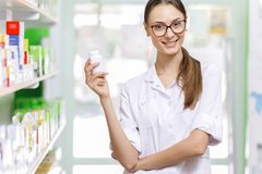 A youthful thin brown-haired lady with glasses,dressed in a lab coat,is holding a small jar in her right hand in a new stock photo
