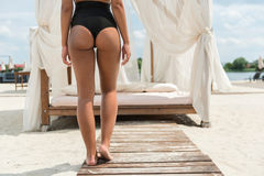 Youthful woman resting on summer beach. Close up of back of young lady in bikini standing on wooden path to her chic sunbed with soft pillows, mattress and Stock Image