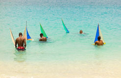 Youths sailing gumboats in the caribbean Stock Photo