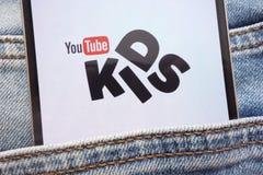 YouTube在智能手机显示的孩子商标掩藏在牛仔裤装在口袋里 免版税库存图片