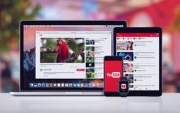 YouTube στο iPhone 7 της Apple υπέρ ρολόι και Macbook της Apple iPad υπέρ Στοκ Φωτογραφίες