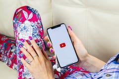 YouTube applikationsymbol på närbild för skärm för smartphone för Apple iPhone X i kvinnahänder Youtube app symbol Social massmed Arkivfoton