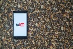 Youtube-Logo auf Smartphone auf Hintergrund von kleinen Steinen Stockfotografie