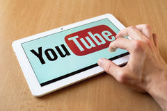 Youtube. Man's hand use with his fingers tablet. Youtube app is on the screen. Youtube is popular video-sharing website Royalty Free Stock Image