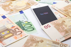 Youtube monetization. Smartphone and banknotes Stock Photography