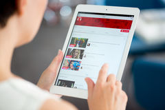 YouTube music playlist on Apple iPad Air. KIEV, UKRAINE - MAY 21, 2014: Woman holding a brand new Apple iPad Air and looking on  YouTube music playlist on a Stock Image