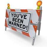 Youve Been Warned Road Construction Sign Danger Warning. You've Been Warned words on a blockade or road construction barrier sign to illustrate danger, peril or Royalty Free Stock Photography