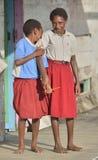 YOUW-BY, ATSY-OMRÅDE, ASMAT-REGION, IRIAN JAYA, NEW GUINEA, INDONESIEN - MAJ 23, 2016: Skolbarn i likformig Liten vill Arkivbild