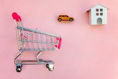 Yoy house and car in shopping cart on pink background. Small supermarket grocery push cart for shopping toy miniature white house and car on pink pastel color stock photography