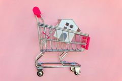 Yoy house in shopping cart on pink background. Small supermarket grocery push cart for shopping toy miniature white house on pink pastel color paper flat lay royalty free stock image