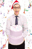Yoyful young man with Santa hat holding a cake Royalty Free Stock Images