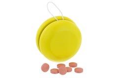 Yoyo amarillo al lado de medicinas rosadas Fotos de archivo
