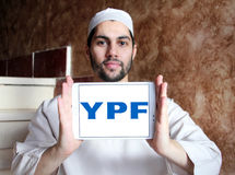 YPF, Fiscal Oilfields oil and gas company logo. Logo of Argentine oil company YPF, Fiscal Oilfields on samsung tablet holded by arab muslim man . YPF, Fiscal Royalty Free Stock Photos