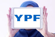 YPF, Fiscal Oilfields oil and gas company logo. Logo of Argentine oil company YPF, Fiscal Oilfields on samsung tablet holded by arab muslim woman . YPF, Fiscal Royalty Free Stock Photography