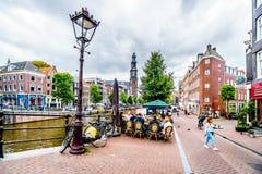 Ypicalscène van zich het verzamelen van toeristen en plaatselijke bewoners bij een koffie bij het Prinsengracht-kanaal in Amsterd stock foto's