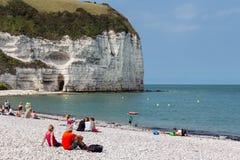 Seaside visitors sitting at beach near limestone cliffs Yport, France royalty free stock photos