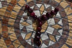 Ypsilon machte mit cherrys, um einen Buchstaben des Alphabetes mit Früchten zu bilden Stockbilder