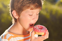 Ypung boy eating donut outdoors. Teenager boy eating pink glazed donut outdoors at green background Stock Photography
