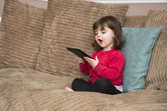 Ypung girl watching tablet PC royalty free stock photos