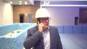 Yrke, affär och telekommunikationer, arkitekt som talar på mobiltelefonen och går i konstruktionsplats lager videofilmer