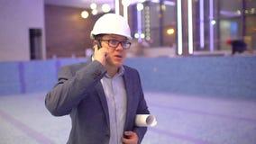 Yrke, affär och telekommunikationer, arkitekt som under talar på mobiltelefonen på bakgrunden av pölen arkivfilmer