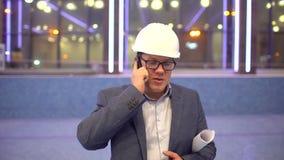 Yrke, affär och telekommunikationer, arkitekt som under talar på mobiltelefonen på bakgrunden av pölen stock video