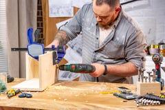 Yrke-, snickeri-, träverk- och folkbegrepp - snickare med plankan för borrande för elektrisk drillborr den wood på seminariet fotografering för bildbyråer