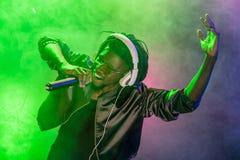 yrkesmässig afrikansk amerikanklubbadiscjockey i hörlurar som sjunger med mikrofonen arkivfoton